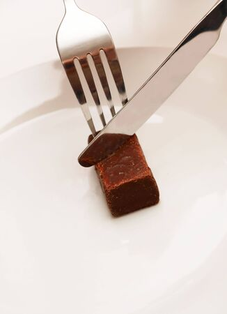 A little chocolate bar on a white plate with fork and knife