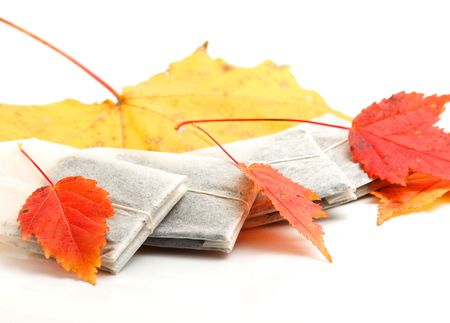 Tea bags laying with autumn leaves on white background Stock Photo