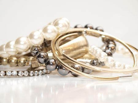 Pearls and ear rings in assorted colors in a pile on white background with reflection