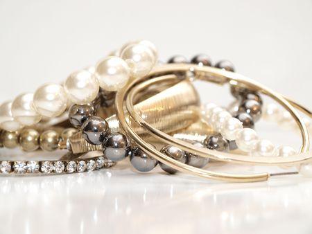 Perlen und Ohr Ringe in verschiedenen Farben in einem Stapel auf weißem Hintergrund mit Reflektion
