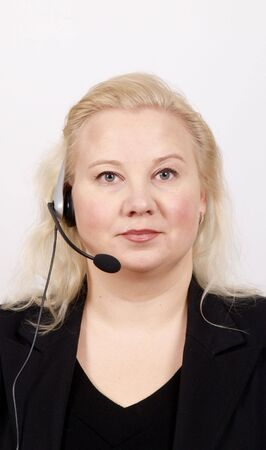 Woman at a helpdesk with headset, dressed in a business suit, serious face while looking at the camera photo