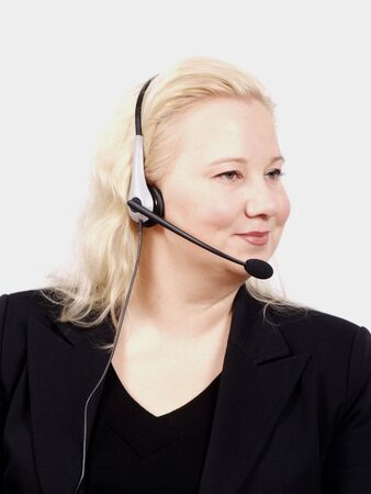 Woman at a helpdesk with headset, dressed in a business suit, smiling while looking to the right photo