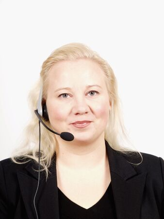 Woman at a helpdesk with headset, dressed in a business suit, smiling while looking at the camera photo