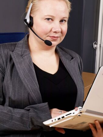 Woman at a helpdesk with white laptop and headset, dressed in a business suit, serious while looking at the camera photo