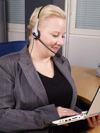 Woman at a helpdesk with white laptop and headset, dressed in a business suit, smiling while watching the PC photo