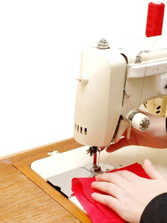 Sewing, white sewingmachine on white background with a little red clothing  photo