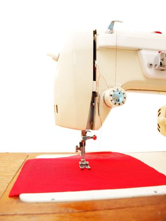 swaddling: Sewing, white sewingmachine on white background with a little red clothing