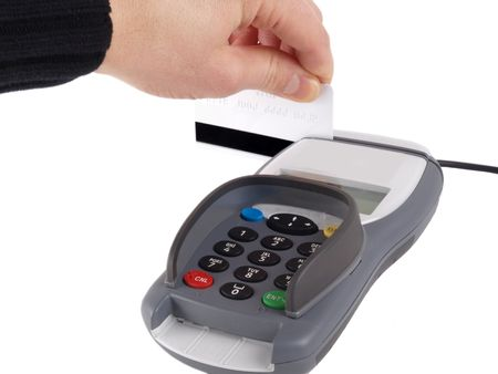 Someone dragging a debit-/credit-card with magnet strip into a payment terminal, on white background Standard-Bild
