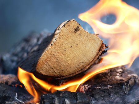 A log burning, flames and smoke on a bonfire