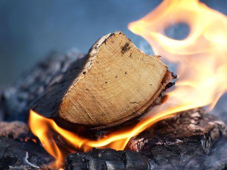 A log burning, flames and smoke on a bonfire