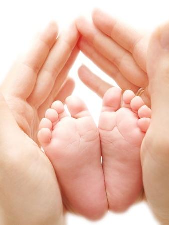Babys Füße zwischen Eltern Hände nach weißem Hintergrund
