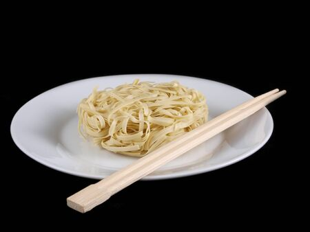 Uncooked noodles, on white plate, with chopsticks, isolated towards black background photo