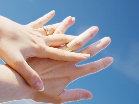 De holdingshanden van het echtpaar naar verse blauwe hemel
