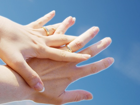 women subtle: Married couple holding hands towards fresh blue sky