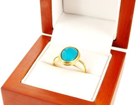 Blue gemstone on gold ring in a wooden box, isolated towards white