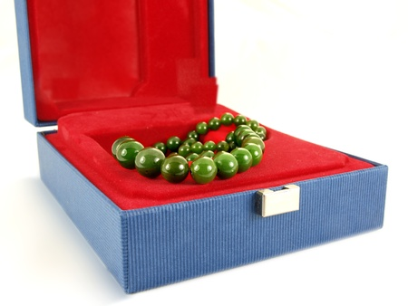 Green gemstone necklace, inside a jewelry box, isolated towards white background photo