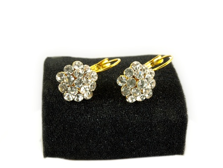 Diamond earrings on black sponge, isolated towards white background photo