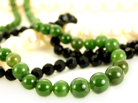 Green gemstone, white pearls, and black pearl necklace, isolated towards white background Stock Photo - 13040550
