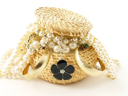 Basket full of jewelery, towards white background Stock Photo