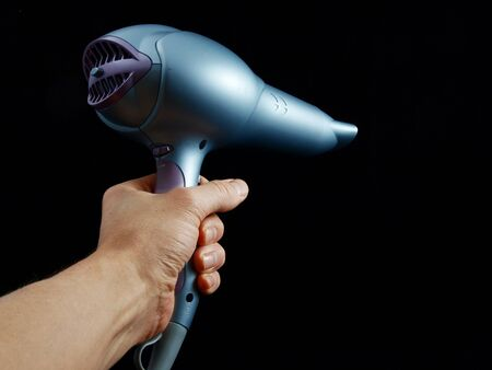 Silver colored hairdryer held by hand, towards black
