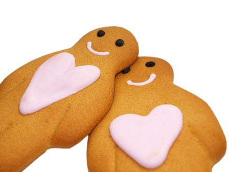 Couple of gingerbread people, with hearts, towards white photo