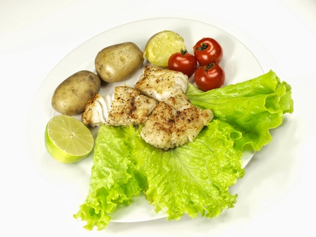 Fried white fish on a plate, with potatoes, salad, lime and tomatoes photo
