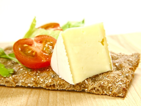 Cracker on wooden board, with soft cheese and tomato photo