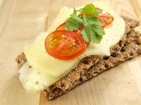 Cracker isolated on wooden plate, with cheese, tomato and parsley photo
