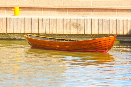 A wooden rowing boat tide down at harbor photo