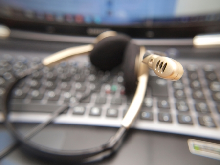 Closeup of microphone on headset, laying on a computer keyboard