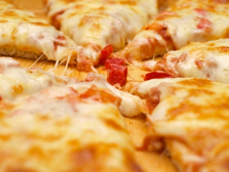 Sliced fresh pizza with red pepper on wooden board Stock Photo - 14529822