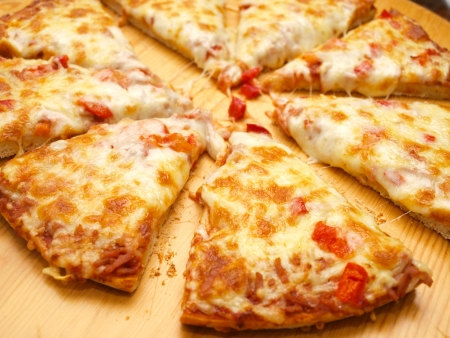 Sliced fresh pizza with red pepper on wooden board Stock Photo - 14529840