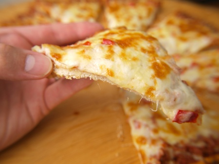 Slice of pizza, held up by a person Stock Photo - 14529813
