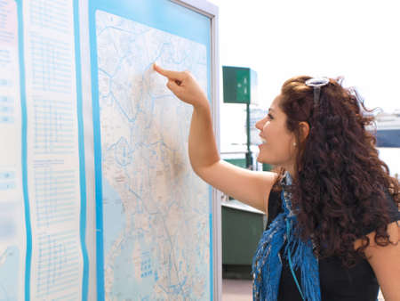 Brunet female smiling and pointing at a map photo