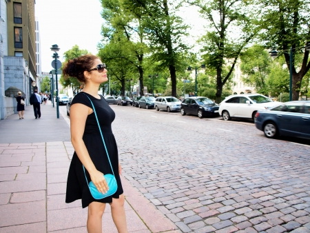 Beautiful brunet, black dress, waiting on the sidewalk photo