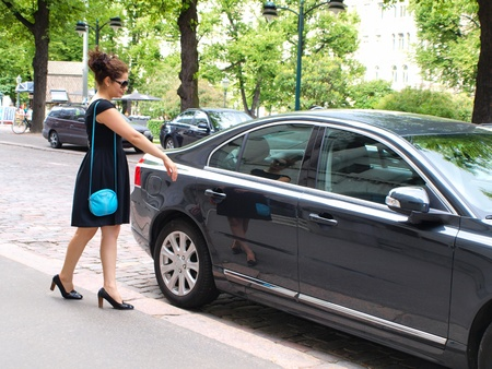Brunet in black dress, approaching a black car photo