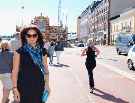 Schöne Brünette, posiert mit Sonnenbrille in einer ländlichen Stadt