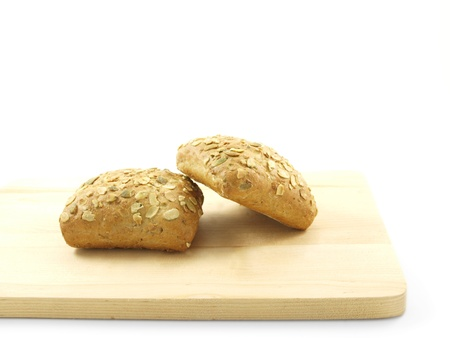 Bread with seeds isolated on a wooden board