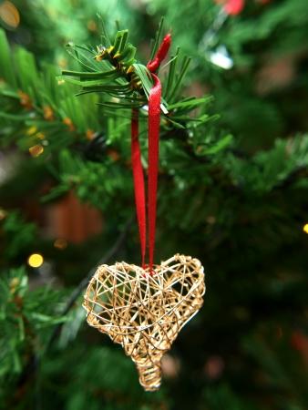 Golden heart ornament hanging on a Christmas tree Standard-Bild