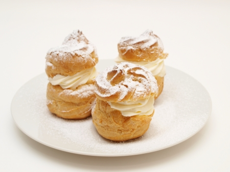 Choux pastry buns, filled with whipped cream, on a plate Stock Photo