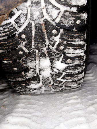 winter tire tracks in snow, closeup, focus on tire photo
