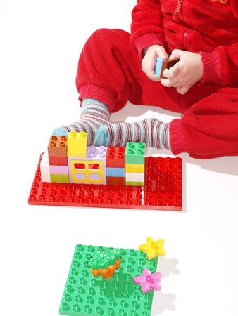 Unrecognizable kid in red, playing with colorful plastic quick build toys photo