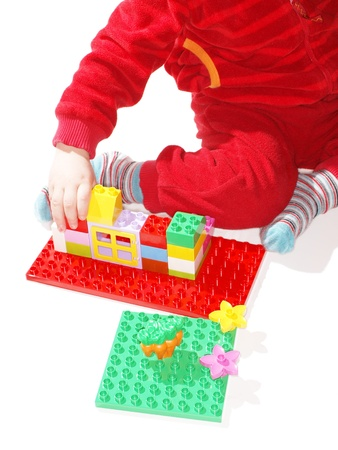 Unrecognizable kid in red, playing with colorful plastic quick build toys Stock Photo - 17805175