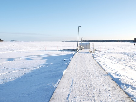natural ice pastime: Ice swimming place, pier covered with snow, blue sky