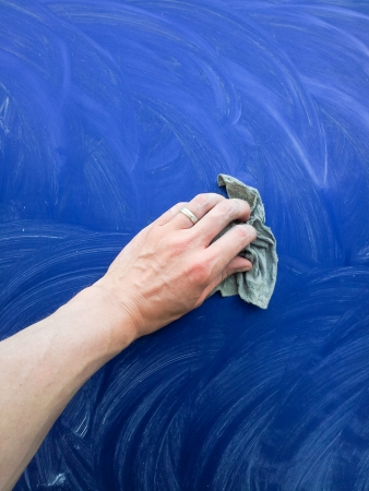 Person working on polishing a blue car Stock Photo
