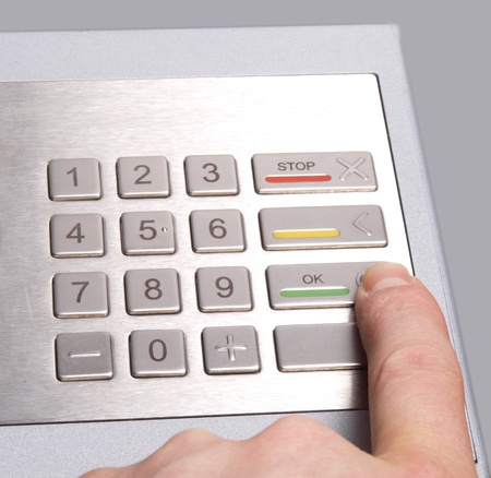 checking accounts: Person using an ATM machine, pressing the green OK button