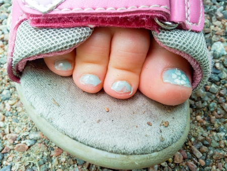 Beautiful blue pedicure on a child in sandel Stock Photo
