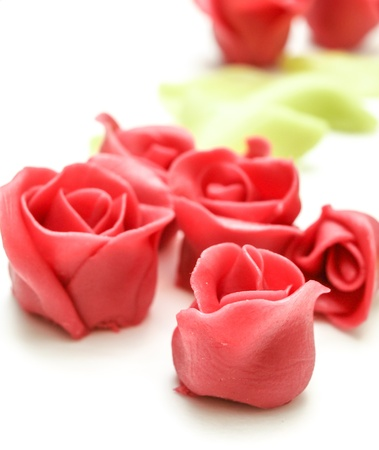 marzipan: Pink marzipan roses towards white with green petals in the background Stock Photo