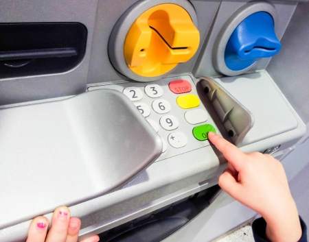 Minor at ATM machine, pressing the green OK button Stock Photo