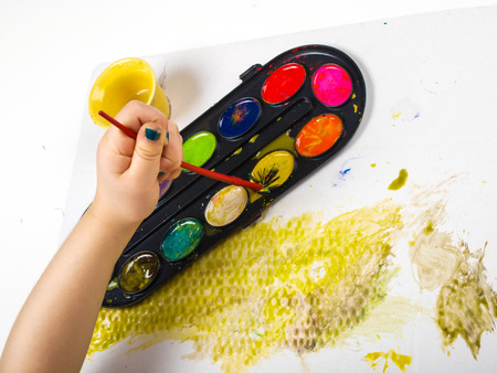 pencils  clutter: Little girls hands playing with colorful paint, creating Easter decoration Stock Photo